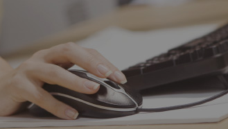Woman's hand clicking on a computer mouse lying next to a keyboard