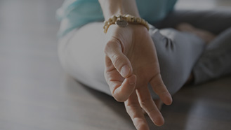 Focus on the arm of a woman in yoga position doing yoga